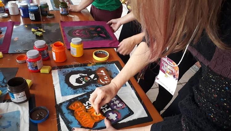 Em um plano fotográfico fechado, aparece uma mesa em que há pessoas fazendo atividades, como desenho e stêncil, com tintas.