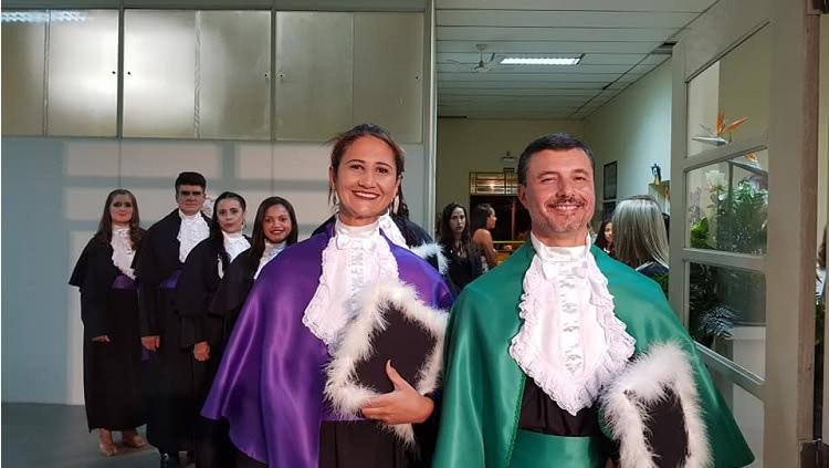 Professores na fila a frente da turma de alunos. Os dois estão com as vestes de patrono e paraninfa e sorriem.
