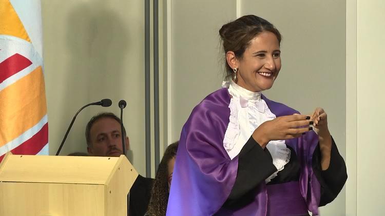 Professora com a roupa de paraninfa atrás do púlpito fazendo seu discurso. Ela está olhando para o lado, onde está a mesa de autoridades e seus alunos afilhados. A professora está sorrindo. No púlpito tem dois microfones. Ao lado aparece uma parte da bandeira da FURG.