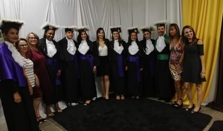 Treze pessoas estão em pé posicionados para foto. Paraninfa está na ponta da foto. Junto aos alunos formandos tem outros professores da turma.