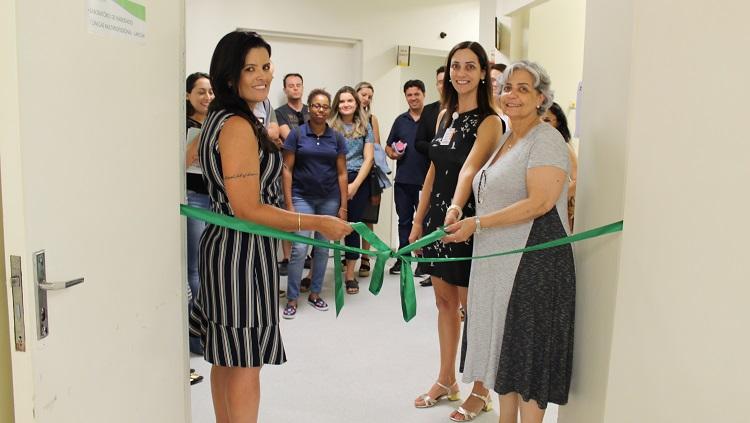 Duas mulheres cortam uma fita verde simbolizando a inauguração do espaço