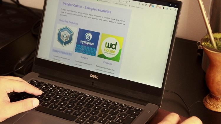 A foto mostra um computador notebook ocupando quase todo o enquadramento. Aparece uma mão sobre o teclado, à esquerda. À direita, há uma mão sobre o mouse do computador. Ao lado direito do computador aparece uma cuia de chimarrão. Na tela está escrito